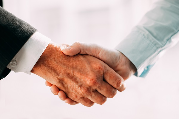Close-up of unrecognizable business partners shaking hands after concluding of deal. Businessmen greeting each other. People making handshake after signing of contract. Business relationship concept